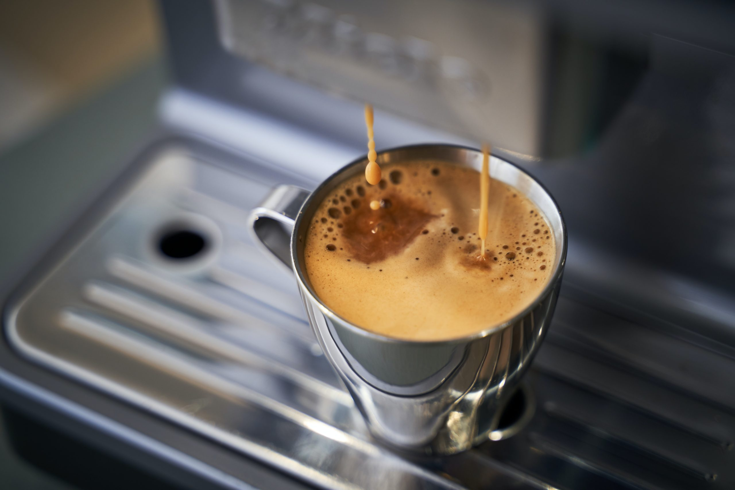 coffee being extracted into a stainless steel cup