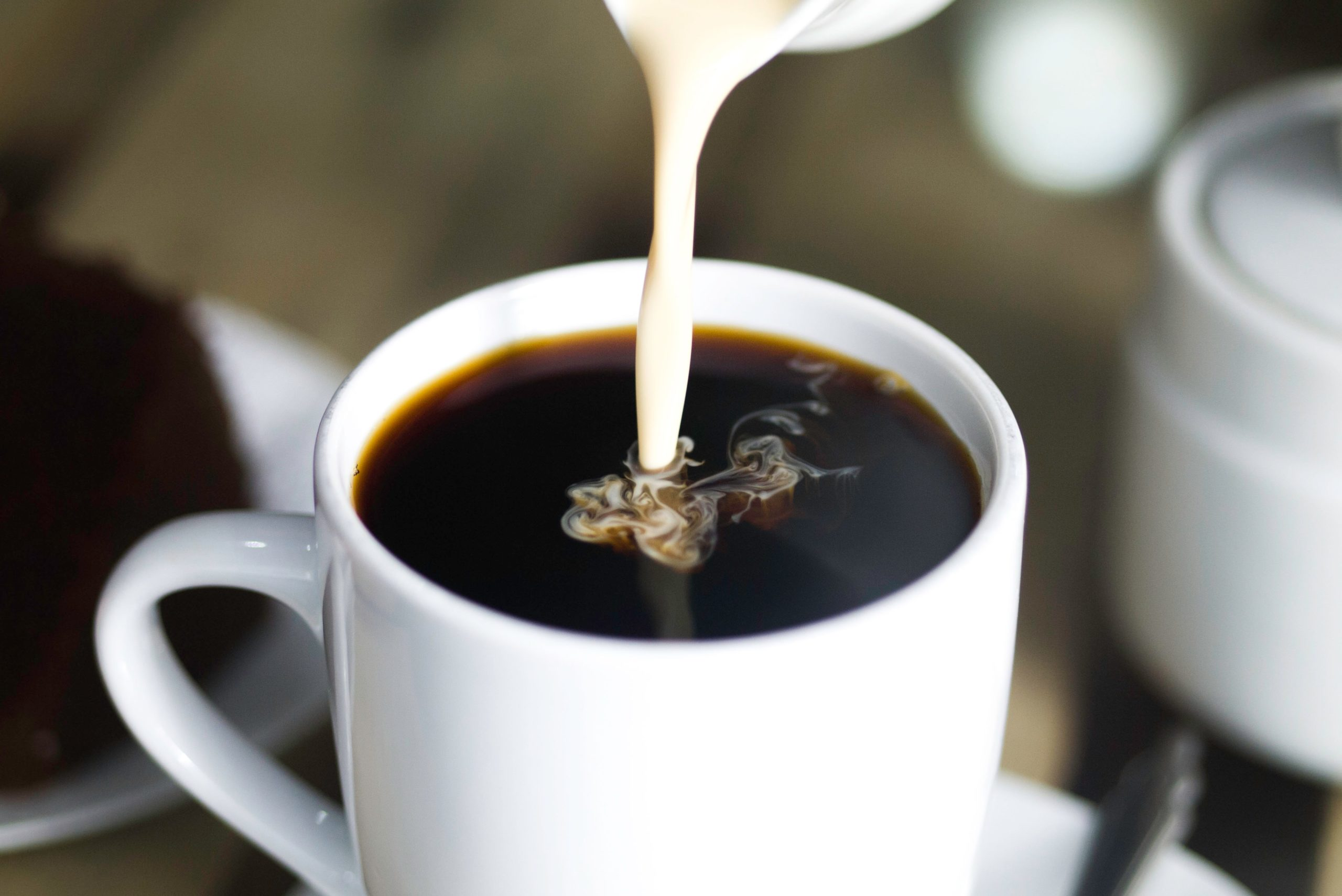 pouring milk into a cup of coffee