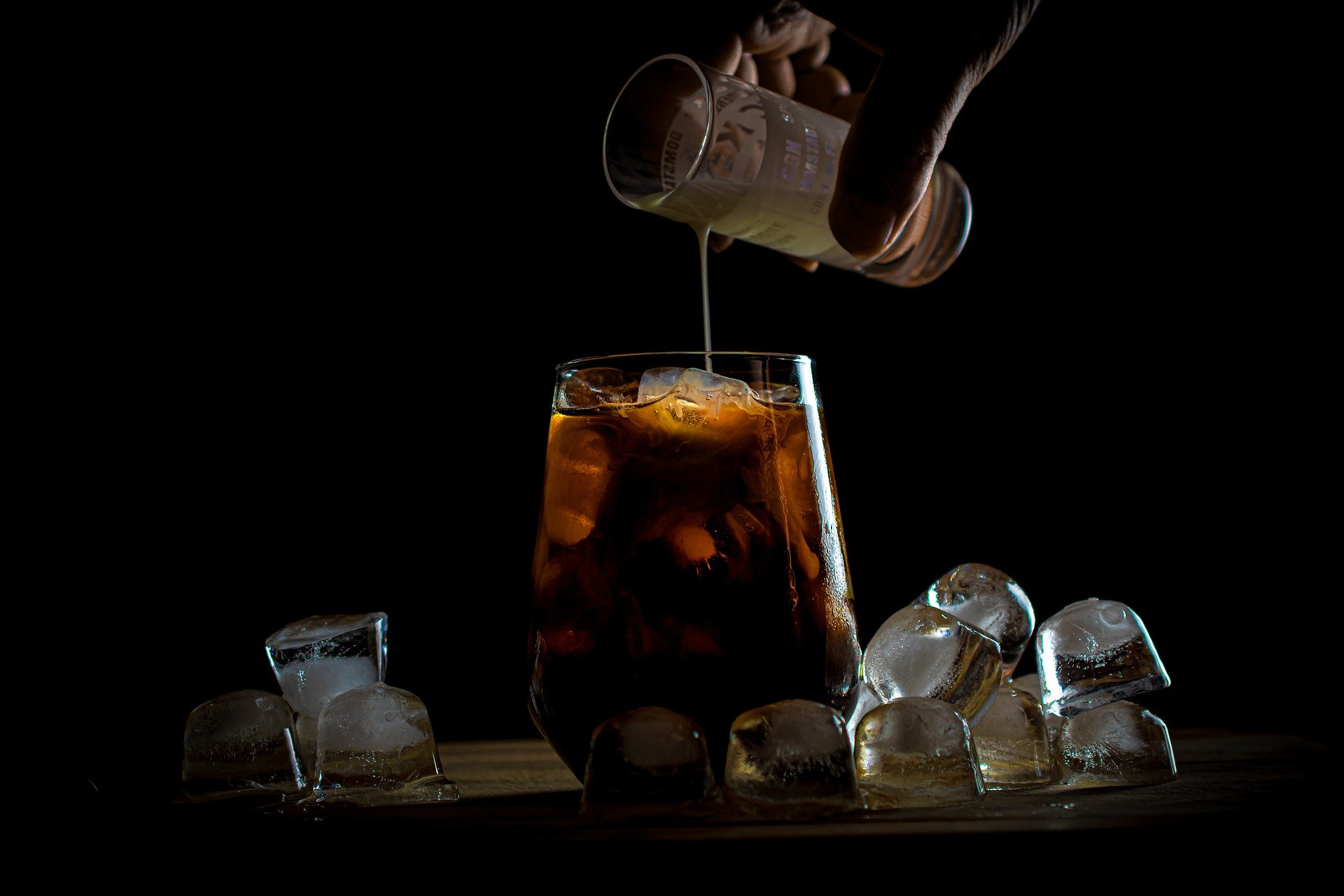 pouring syrup into a cup of iced coffee
