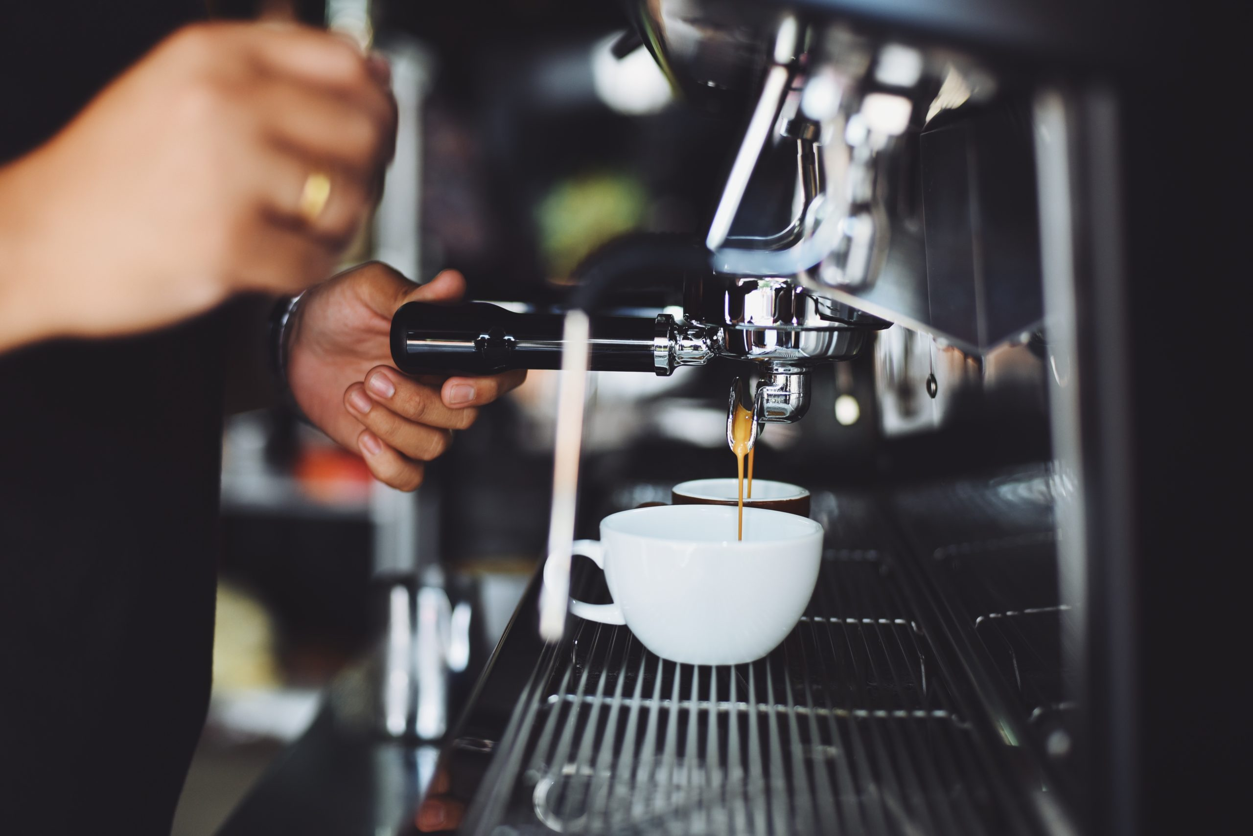 a person extracting coffee from a machine