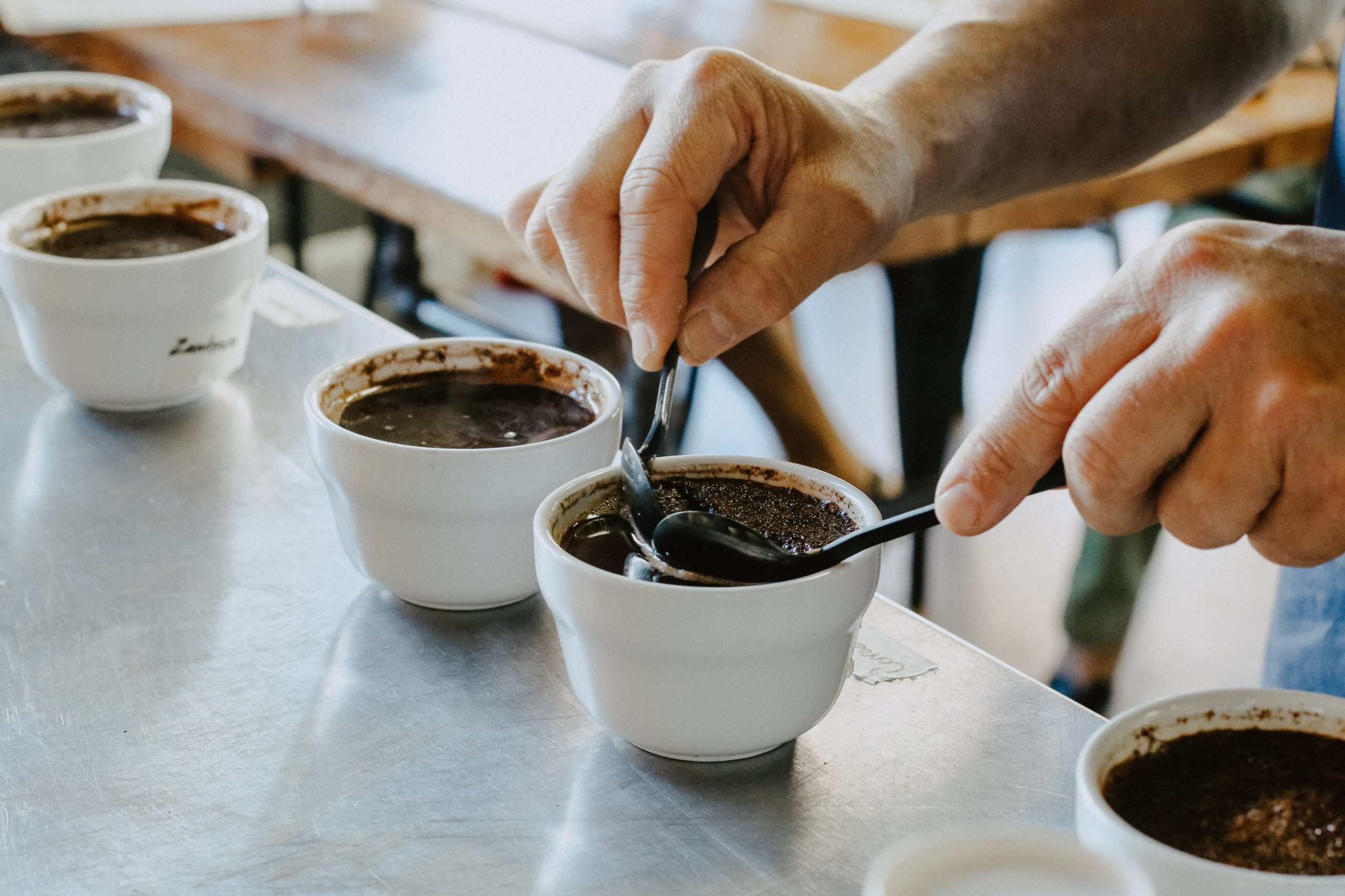 a person carrying out a coffee cupping session
