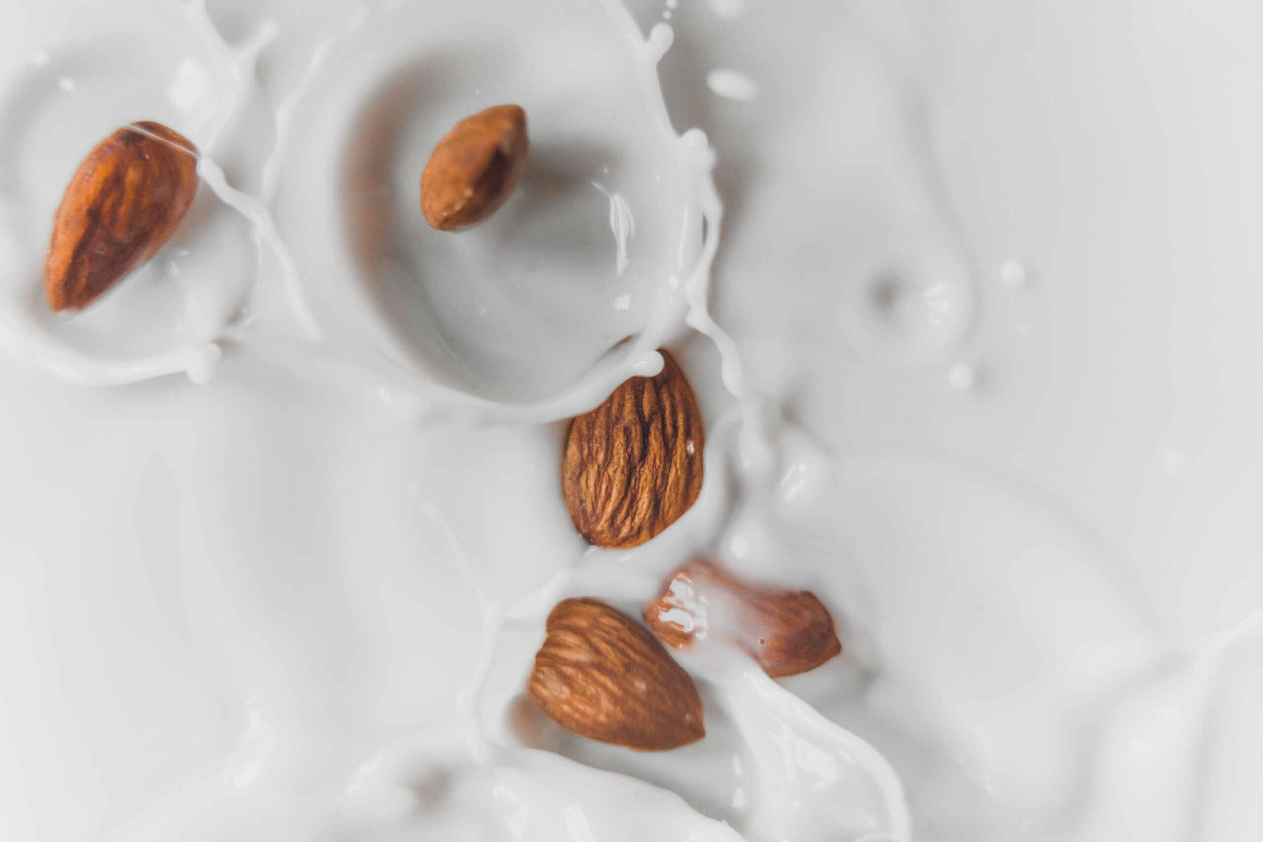 almonds falling into a cup of milk