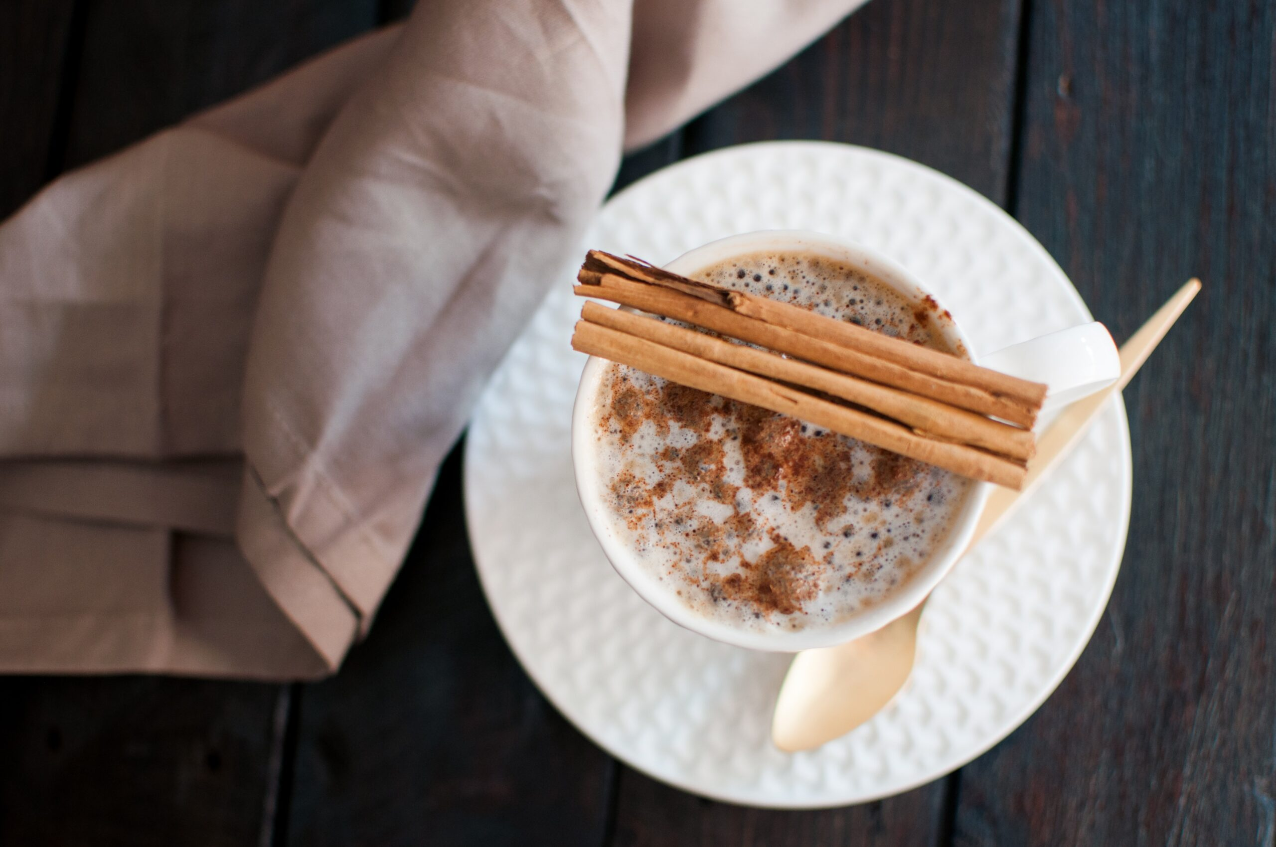a cup of coffee with cinnamon sticks resting on the edge