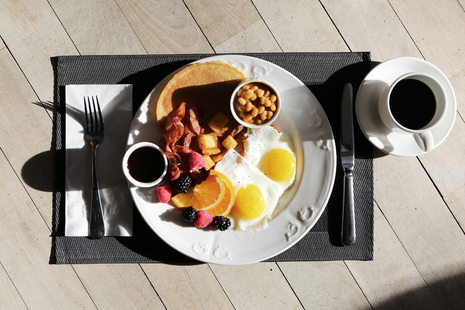 a plate of sunny side ups, baked beans, pancakes
