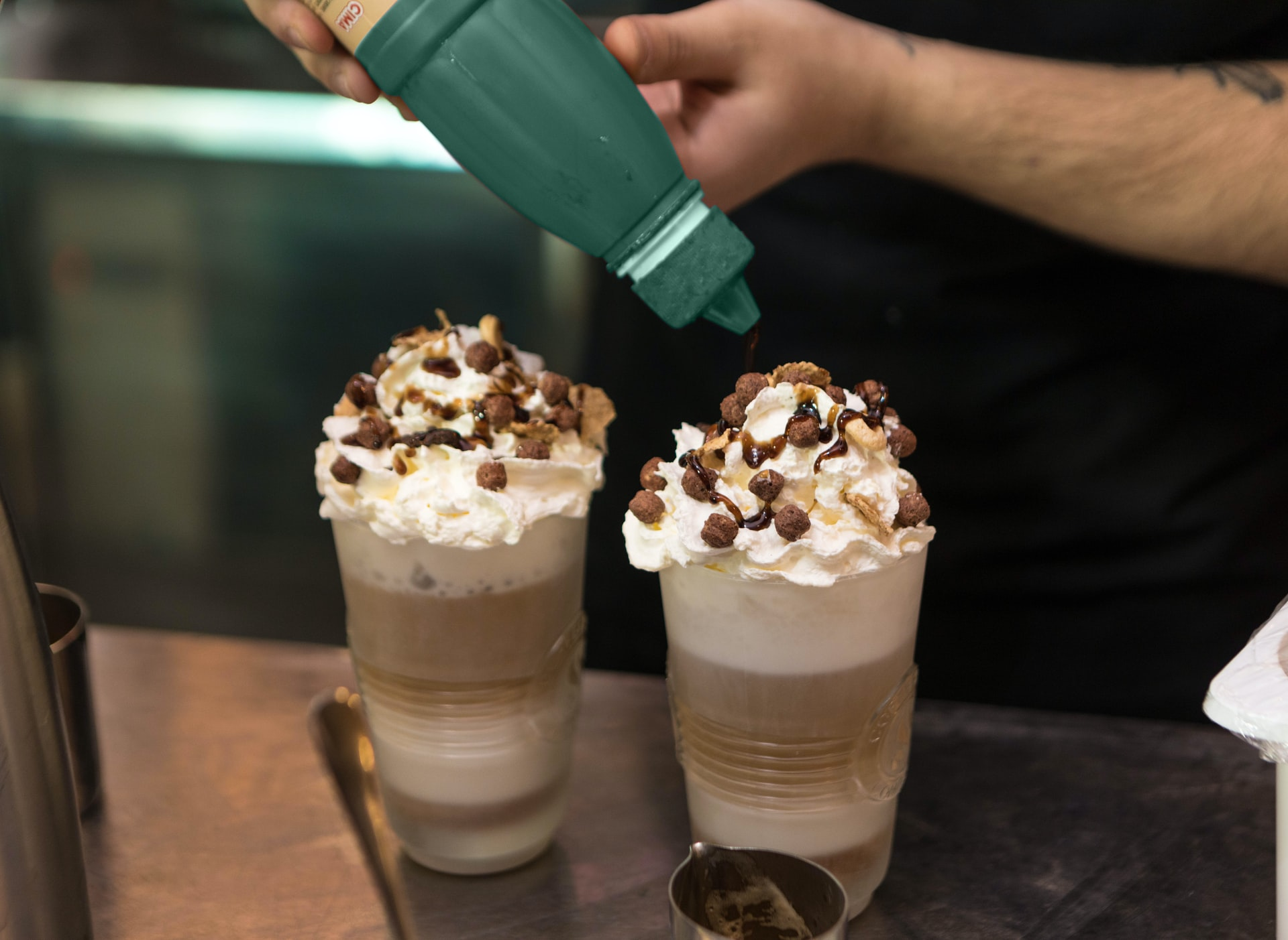 adding chocolate syrup to a coffee drink