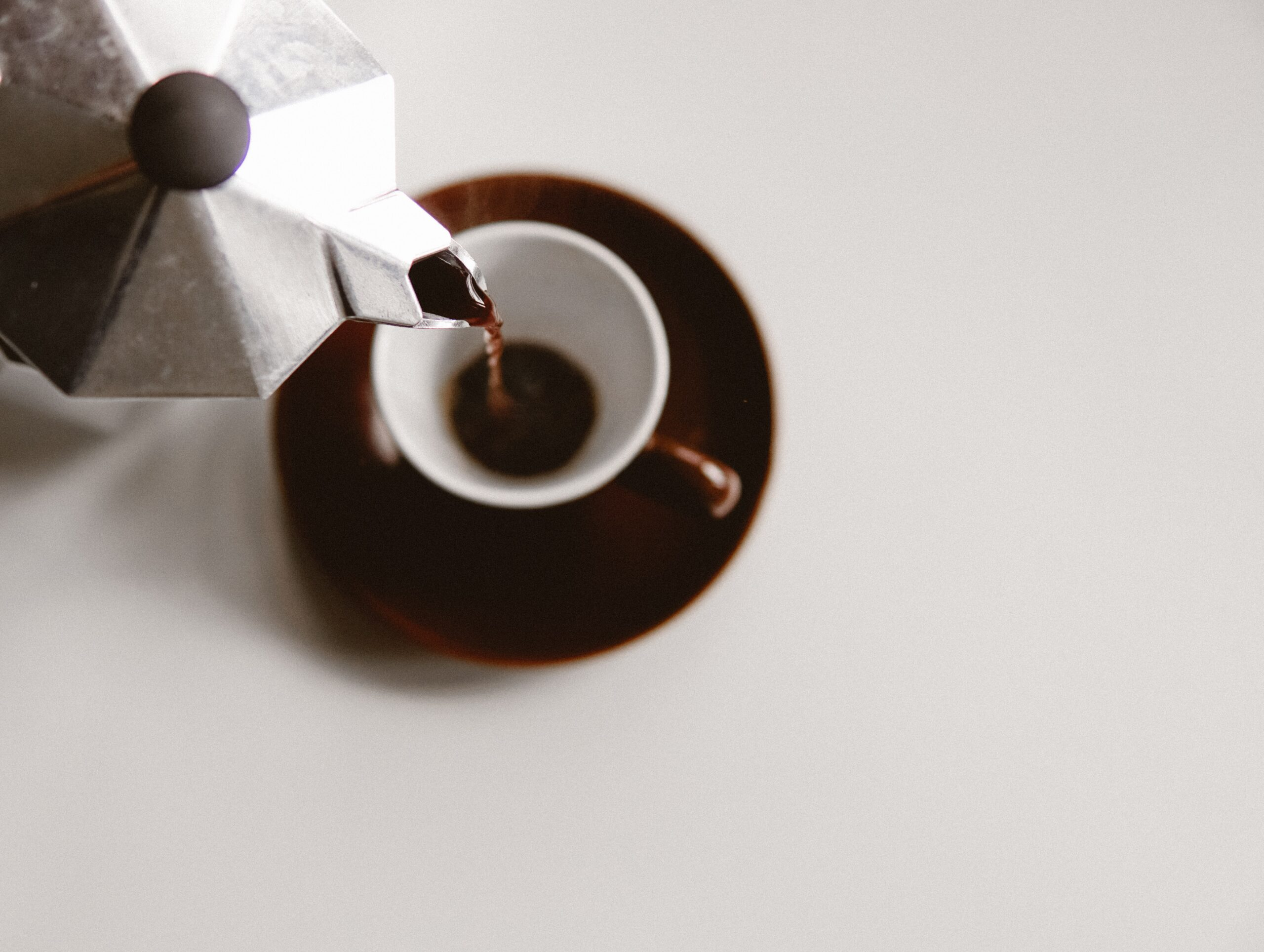 pouring coffee into a cup from a moka pot