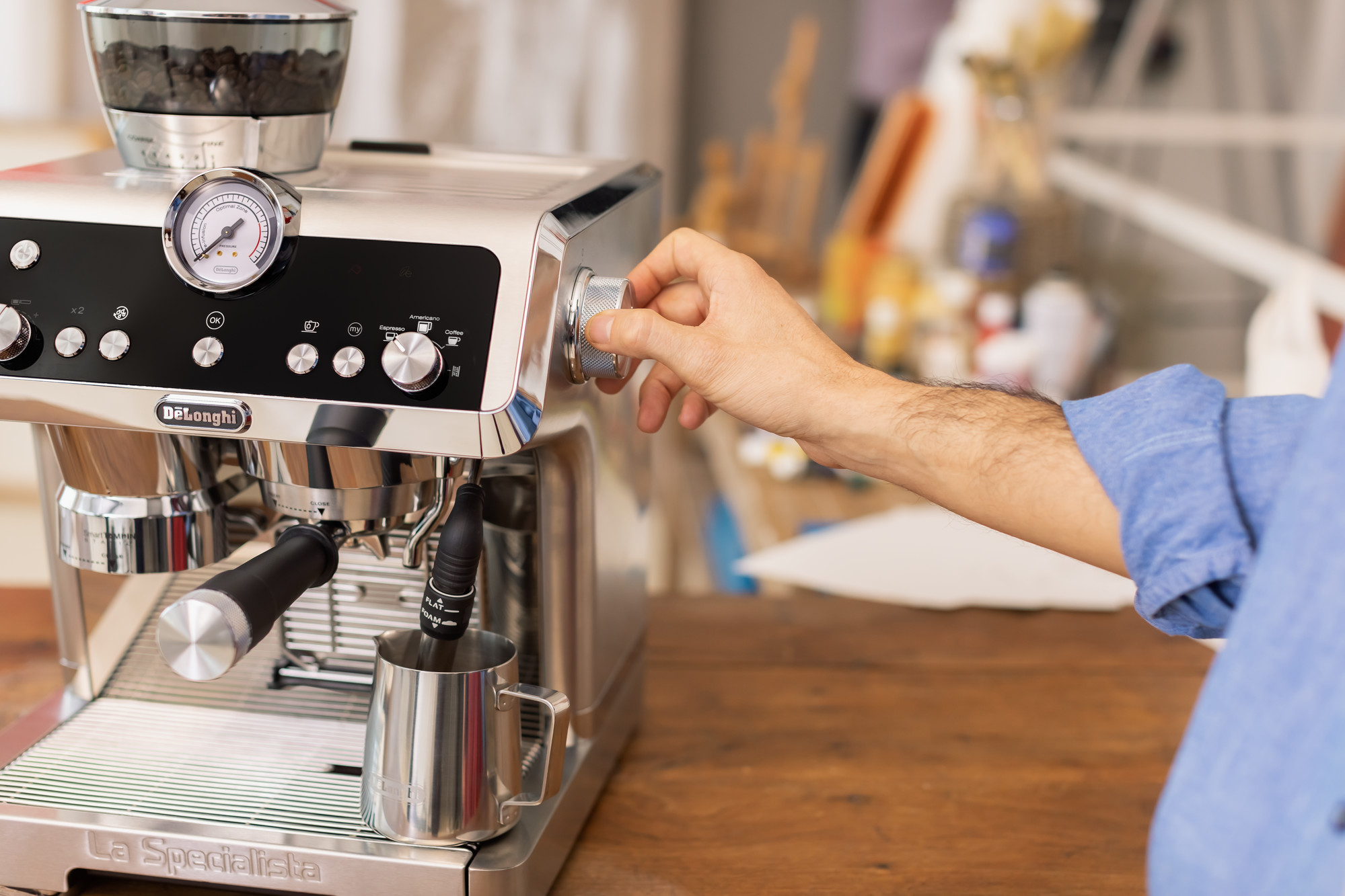person holding a coffee machine's steam wand