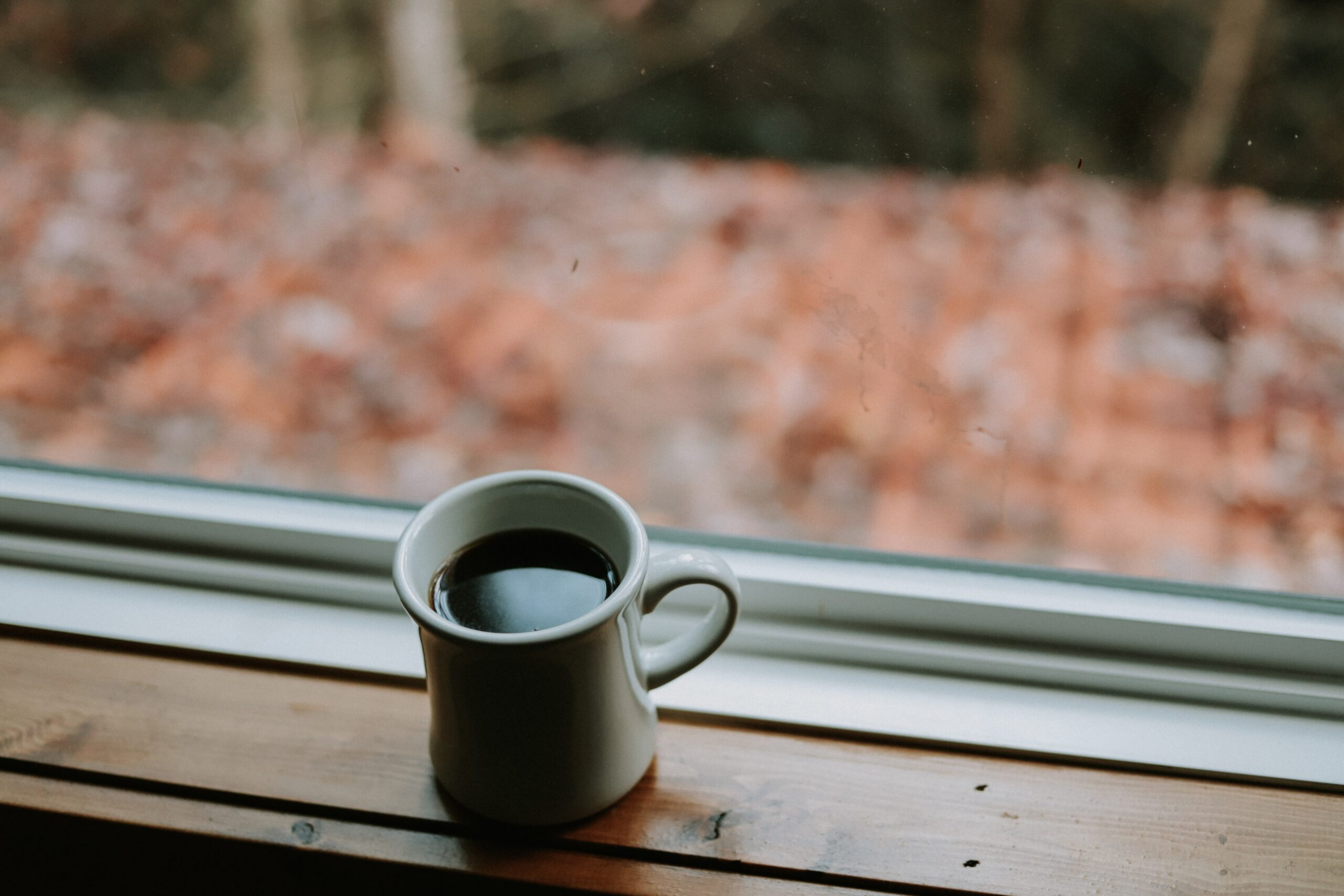 a cup of coffee next to a window