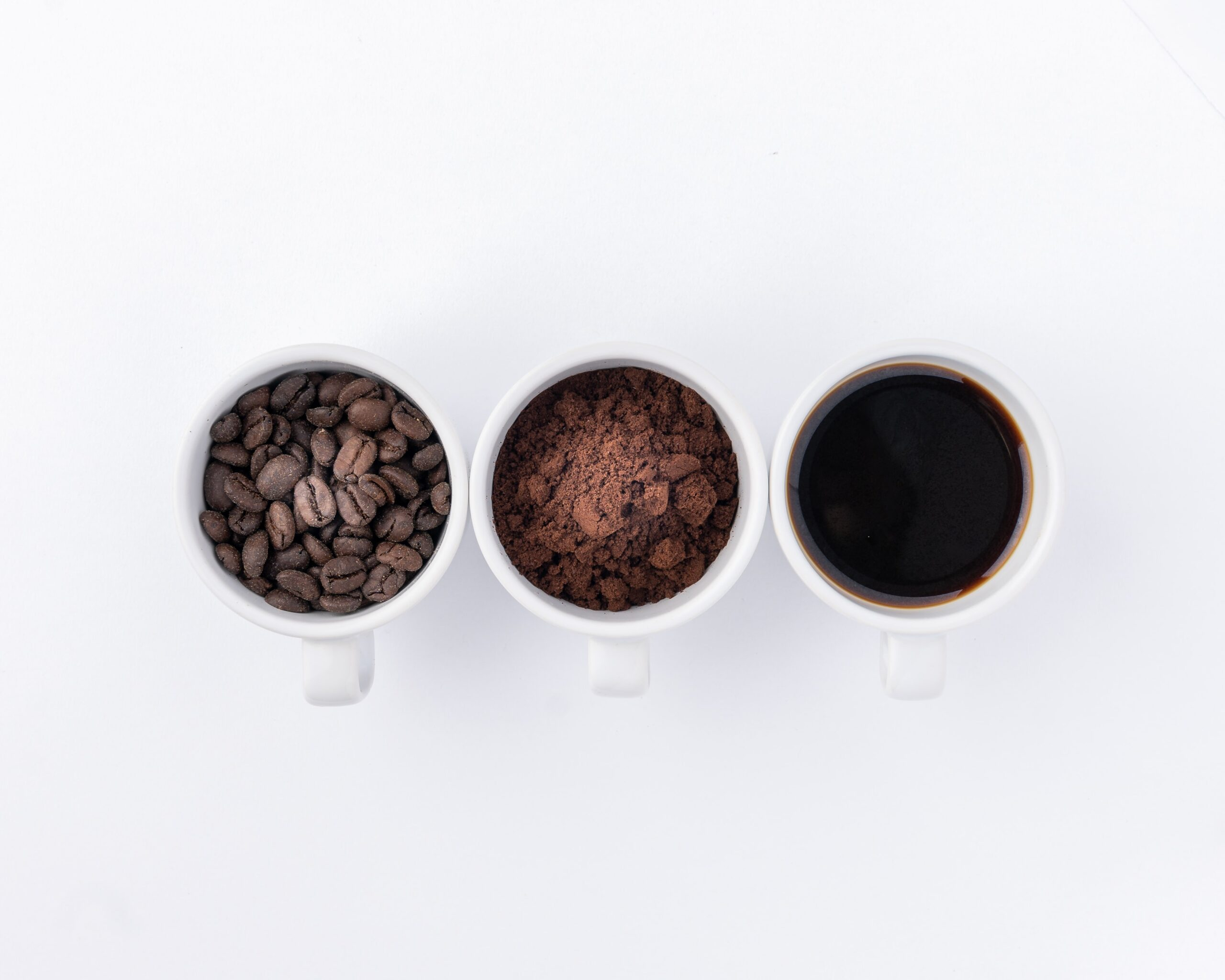 three cups, each filled with coffee beans, grounds, and coffee