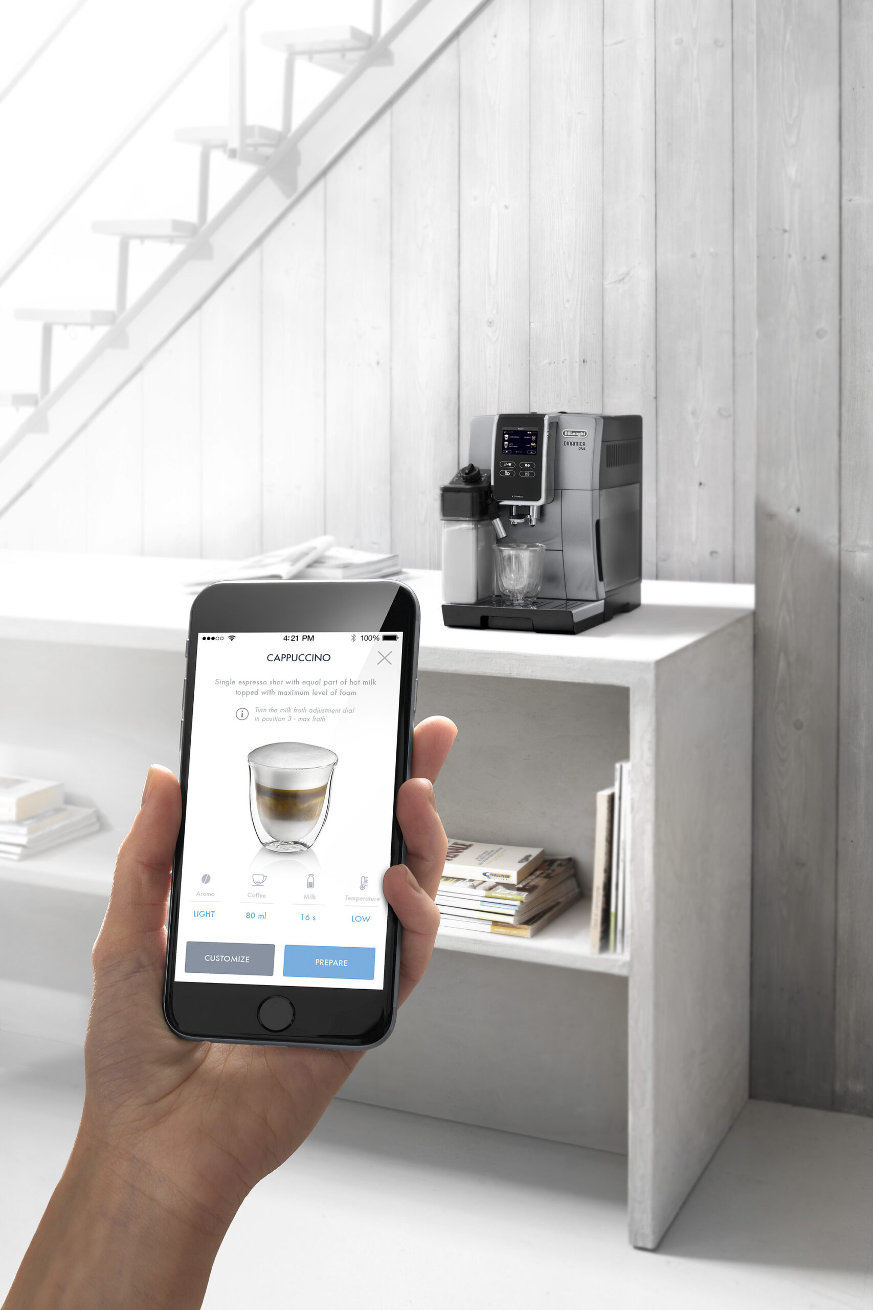 a person holding up a phone in front of a coffee machine
