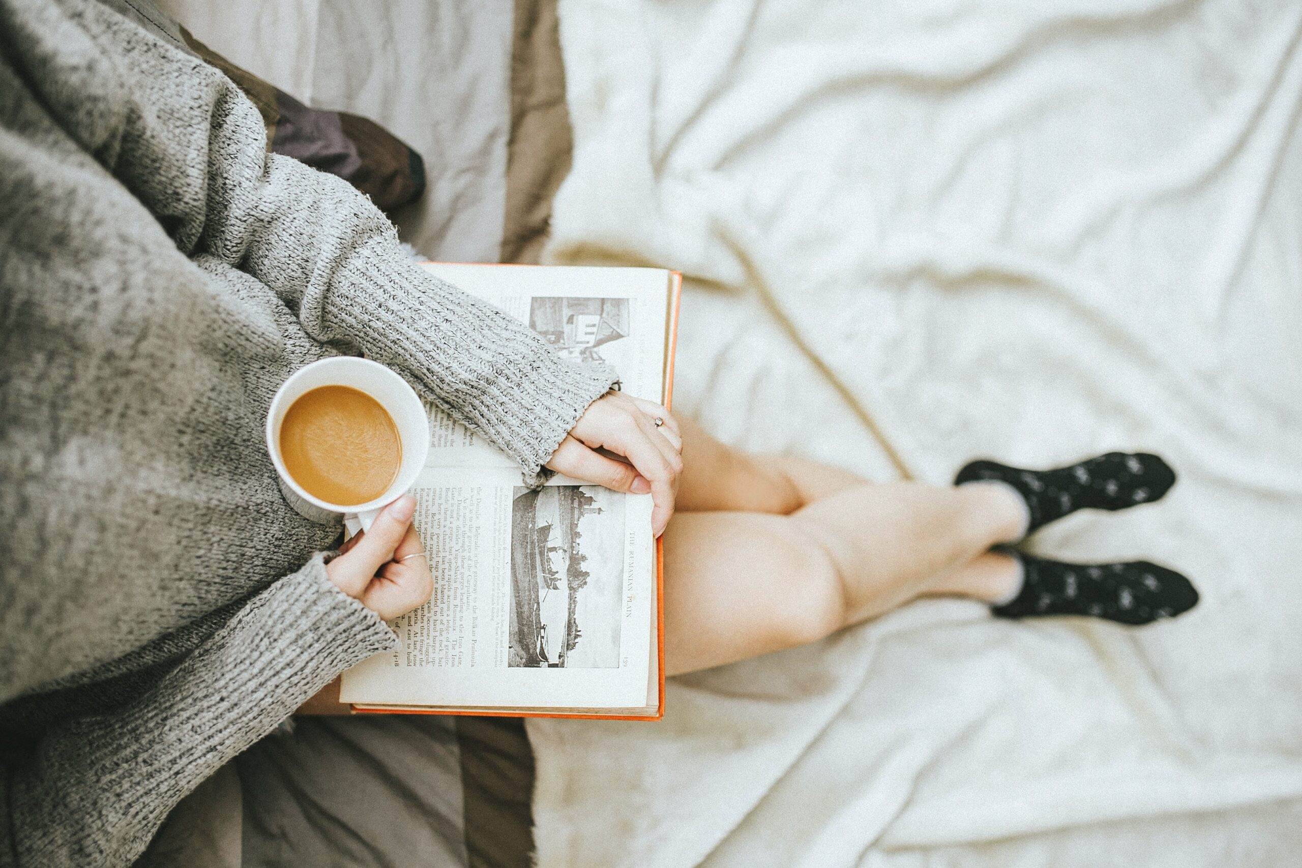 a person reading a book while drinking coffee
