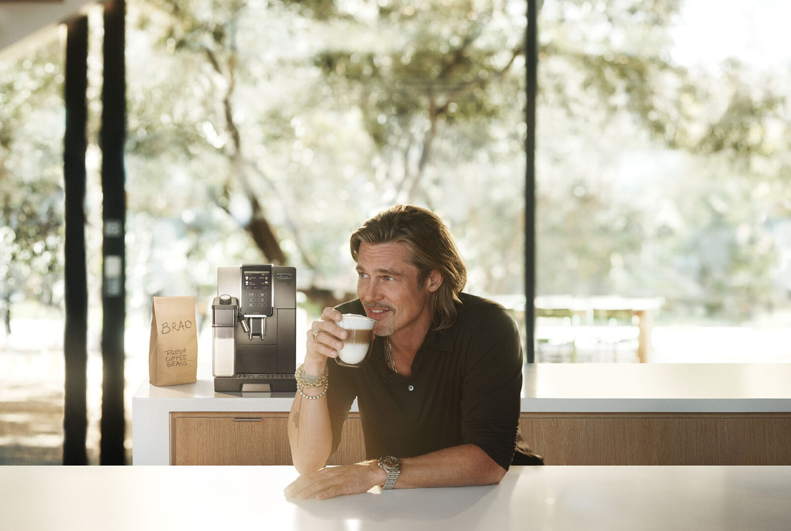 Brad Pitt holding a cup of coffee from De'Longhi