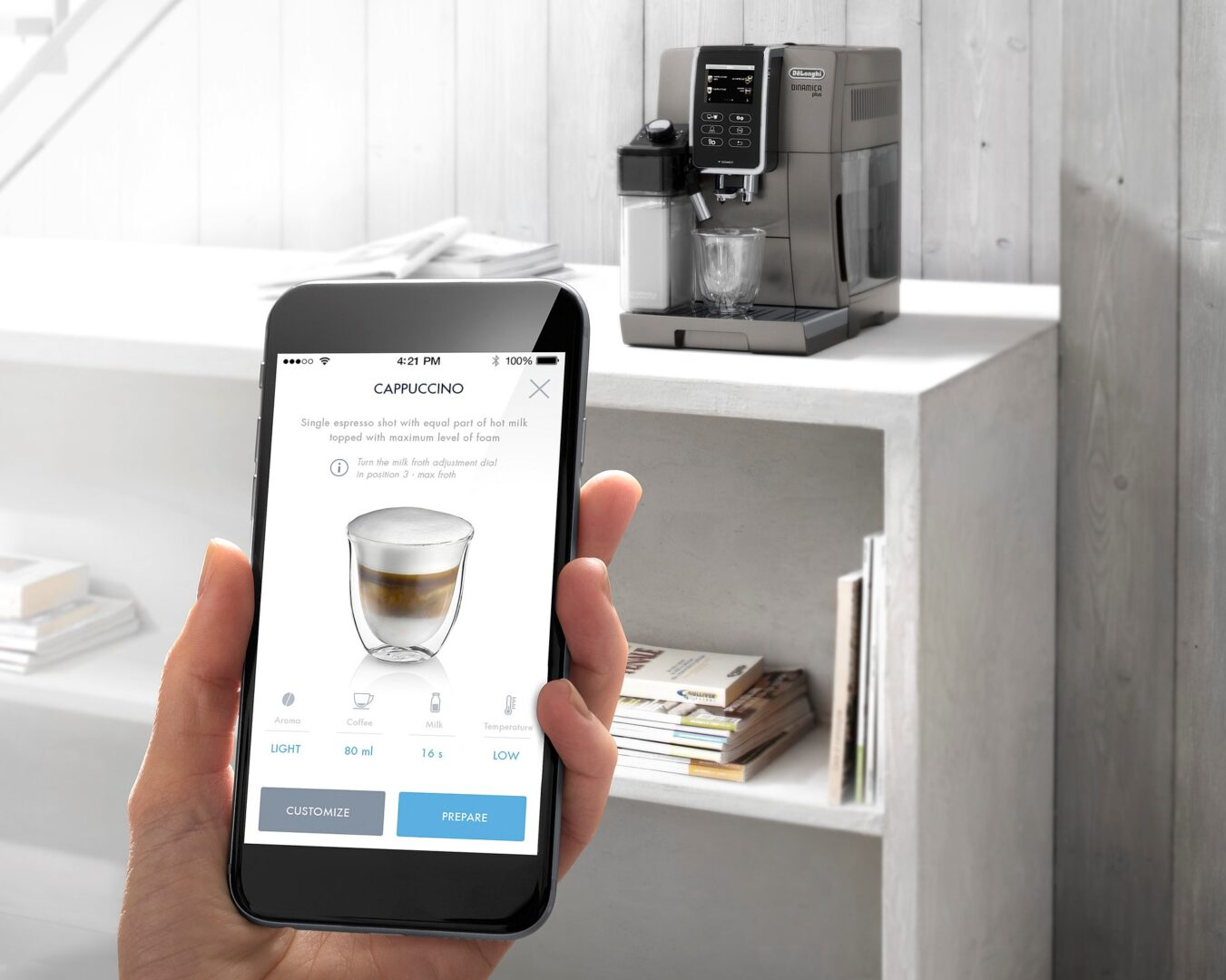 A person holding a mobile phone that shows the De'Longhi Coffee Link App